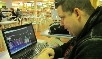 ** FILE ** Joseph Brennen of Ventnor NJ logs on to a Harrah's online casino on his laptop from a highway rest area in Egg Harbor Township NJ on the first day of a test of Internet gambling in New Jersey, Nov. 21, 2013. (AP Photo/Wayne Parry, File)