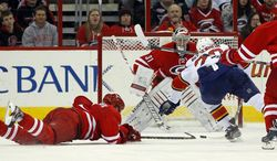 Carolina Hurricanes' Mike Komisarek (5) dives to knock the puck away from Florida Panthers' Sean Bergenheim (20) in front of Hurricanes goalie Anton Khudobin (31), of Kazakhstan, during the second period of an NHL hockey game in Raleigh, N.C., Saturday, Jan. 18, 2014. (AP Photo/Karl B DeBlaker)