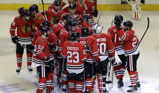 Chicago Blackhawks goalie Corey Crawford (50) celebrates with teammates after the Blackhawks defeated the Boston Bruins 3-2 following their shootout period of an NHL hockey game in Chicago, Sunday, Jan. 19, 2014. (AP Photo/Nam Y. Huh)