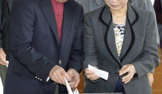 Nago city Mayor Susumu Inamine and his wife Ritsuko cast their ballots in the mayoral election in Nago, on the southern Japanese island of Okinawa, Sunday, Jan. 19, 2014. The small-town mayoral election is being closely watched from Washington to Tokyo as a referendum on long-delayed plans to move a U.S. air base to the community of 62,000 people. Inamine, who opposes the move, faces pro-relocation candidate Bunshin Suematsu in the election. (AP Photo/Kyodo News) JAPAN OUT, CREDIT MANDATORY