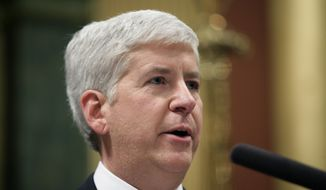 Michigan Gov. Rick Snyder delivers his State of the State address to a joint session of the House and Senate, Thursday, Jan. 16, 2014, in the House Chambers of the state Capitol in Lansing, Mich. (AP Photo/Al Goldis)