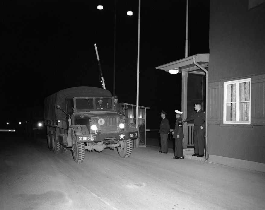 The first of four U.S. Army trucks, detained by Soviet authorities for 54 hours when the Americans refused to have their vehicles inspected, leads the way into West Germany at the Helmstedt check point after release on Feb. 2, 1959. CPL. Richard Masiero of Stockbridge, Mass., the convoy commander, rides the running board to the driver's left as the trunk rolls past two U.S. Military policemen and a West German border guard. (AP Photo/Werner Kreusch)