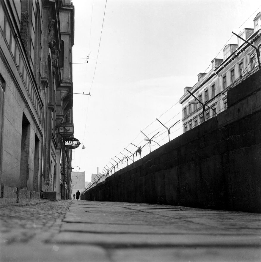 A high wall of concrete blocks, topped with barbed wire, divides Sebastian Strasse in the Kreuzberg district of Berlin, Germany, on Feb. 15, 1962.  To the left is the American sector and beyond the wall to the right is the Russian sector.  (AP Photo)