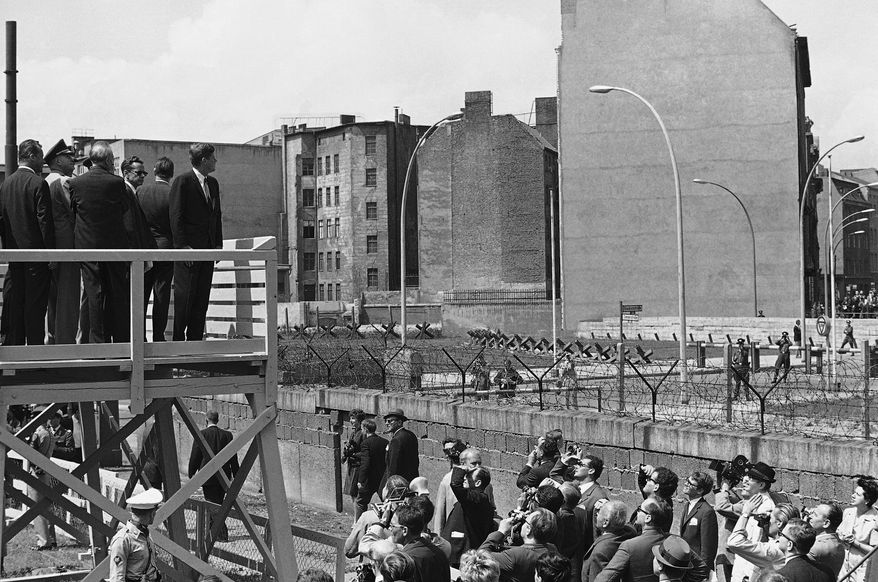 President John Kennedy,standing on observation platform, looks into East Berlin June 26, 1963 across the Communist  Berlin Wall that divides the German city.  Kennedy stands on a tower and looks over the wall into the Berlin side near Checkpoint Charlie.  President Kennedy concluded his German visit later in the day and flew to Ireland for the second leg of his European tour. (AP Photo)