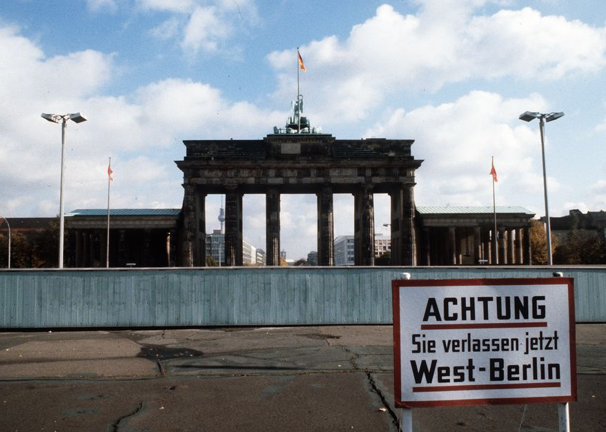 The Brandenburg Gate, one of Berlin's famous landmarks, towers over the Berlin Wall, in 1980. Sign at right reads: Attention: You are now leaving West Berlin. (AP Photo)