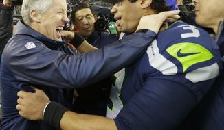 Seattle Seahawks head coach Pete Carroll celebrates with Seattle Seahawks' Russell Wilson after the second half of the NFL football NFC Championship game against the San Francisco 49ers Sunday, Jan. 19, 2014, in Seattle. The Seahawks won 23-17 to advance to Super Bowl XLVIII. (AP Photo/Ted S. Warren)
