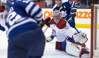 Toronto Maple Leafs left winger Mason Raymond, left, scores on Montreal Canadiens goaltender Carey Price as Joffrey Lupul (19) watches during the second period of an NHL hockey game Saturday, Jan. 18, 2014, in Toronto. (AP Photo/The Canadian Press, Frank Gunn)