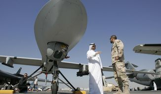 FILE - In this file photo take Monday Nov. 12, 2007, an Emirati visitor asks a question to a military representative as they stand next to an MQ-1 Predator spy plane during the 2nd day of the 10th Dubai Airshow at the Dubai airport, United Arab Emirates. The UAE Prime Minister Sheik Mohammed bin Rashid Al Maktoum said Sunday, Jan. 19, 2014, the Gulf nation has begun the process of imposing mandatory military service for adult males. (AP Photo/Kamran Jebreili, File)