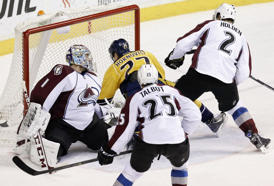 Nashville Predators forward Patric Hornqvist (27), of Sweden, falls into Colorado Avalanche goalie Semyon Varlamov (1), of Russia, as Hornqvist scores a goal in the second period of an NHL hockey game, Saturday, Jan. 18, 2014, in Nashville, Tenn. Also defending for the Avalanche are Maxime Talbot (25) and Nick Holden (2). (AP Photo/Mark Humphrey)