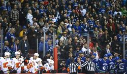 Referees get in the way of Vancouver Canucks head coach John Tortorella as he shouts at the Calgary Flames bench during first-period NHL hockey action in Vancouver, British Columbia, Saturday, Jan. 18, 2014. (AP Photo/The Canadian Press, Jonathan Hayward)