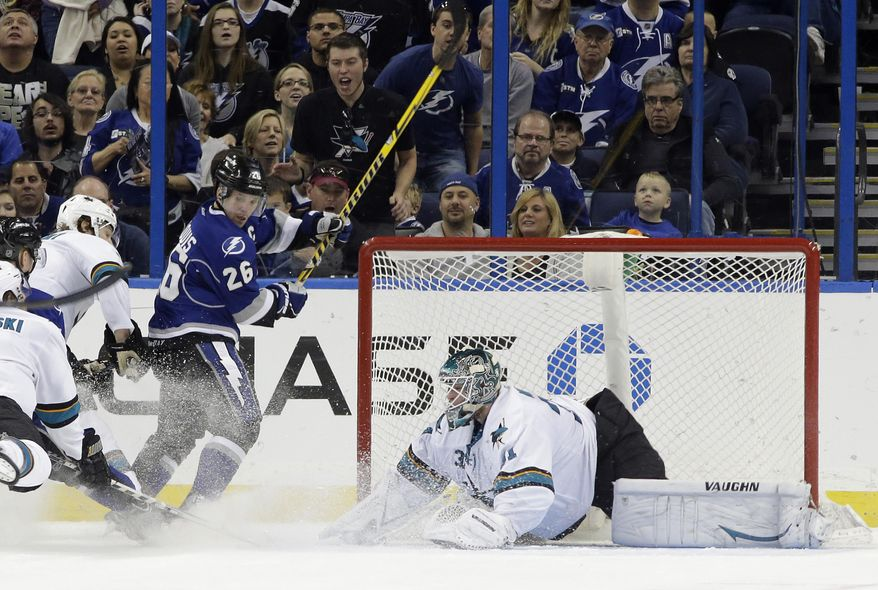 Tampa Bay Lightning right wing Martin St. Louis (26) scores past San Jose Sharks goaltender Antti Niemi (31), of Finland, during the first period of an NHL hockey game Saturday, Jan. 18, 2014, in Tampa, Fla. (AP Photo/Chris O'Meara)