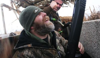 Jason Baker of the Christian-based nonprofit Montana Mallards and Marine Veteran Ike Zahn let out a whoop after Zahn hit two ducks in two shots Friday Jan. 10, 2014. (AP Photo/Ravalli Republic,  Perry Backus)