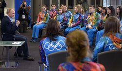 """Russian President Vladimir Putin, left,  speaks at his meeting with Olympic volunteers in the Black Sea resort of Sochi, Russia, Friday, Jan. 17, 2014. Putin says gays should feel welcome at the upcoming Winter Olympic Games in Sochi, but they must """"leave the children in peace."""" Putin told volunteers Friday that gays visiting Sochi """"can feel calm and at ease,"""" and vowed that there would be no discrimination at the games. But he emphasized that, according to a law banning homosexual """"propaganda"""" among minors, gays cannot express their views on gay rights issues to anyone underage. (AP Photo/RIA-Novosti, Alexei Nikolsky, Presidential Press Service)"""