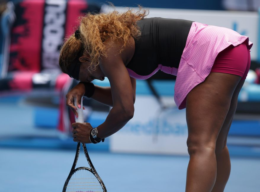 Serena Williams of the U.S. supports herself with a racket as she plays Ana Ivanovic of Serbia during their fourth round match at the Australian Open tennis championship in Melbourne, Australia, Sunday, Jan. 19, 2014.(AP Photo/Aaron Favila)
