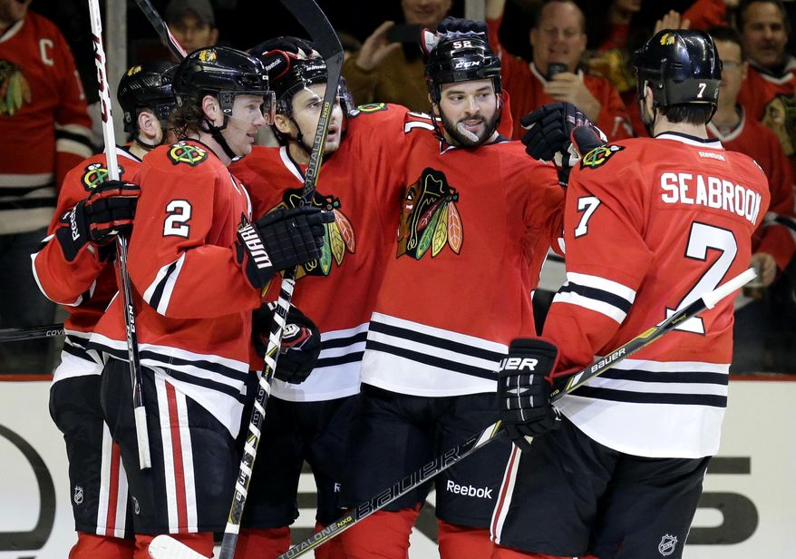 Chicago Blackhawks' Brandon Bollig (52), second from right, celebrates with teammates after scoring a goal during the second period of an NHL hockey game against the Boston Bruins in Chicago, Sunday, Jan. 19, 2014. (AP Photo/Nam Y. Huh)