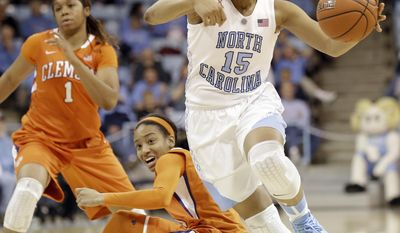 North Carolina's Allisha Gray (15) dribbles past Clemson's Chancie Dunn and Charmaine Tay (1) during the first half of an NCAA college basketball game in Chapel Hill, N.C., Thursday, Jan. 16, 2014. (AP Photo/Gerry Broome)