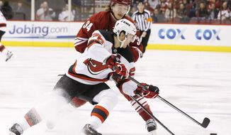 New Jersey Devils' Patrik Elias (26), of the Czech Republic, gets a pass off as he is hit by Phoenix Coyotes' Tim Kennedy (34) during the first period of an NHL hockey game on Saturday, Jan. 18, 2014, in Glendale, Ariz. (AP Photo/Ross D. Franklin)