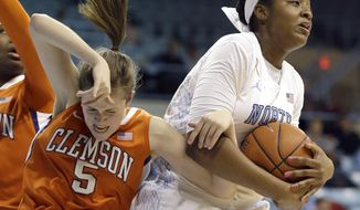 North Carolina's Stephanie Mavunga, right, and  Clemson's Kelly Gramlich (5) struggle for possession of the ball during the first half of an NCAA college basketball game in Chapel Hill, N.C., Thursday, Jan. 16, 2014. (AP Photo/Gerry Broome)
