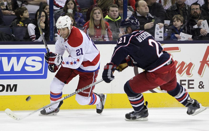Washington Capitals' Brooks Laich, left, and Columbus Blue Jackets' James Wisniewski chase a loose puck during the first period of an NHL hockey game on Friday, Jan. 17, 2014, in Columbus, Ohio. (AP Photo/Jay LaPrete)