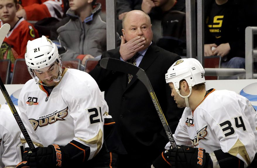Anaheim Ducks coach Bruce Boudreau wipes his face as he watches his team during the first period of an NHL hockey game against the Chicago Blackhawks in Chicago, Friday, Jan. 17, 2014. (AP Photo/Nam Y. Huh)
