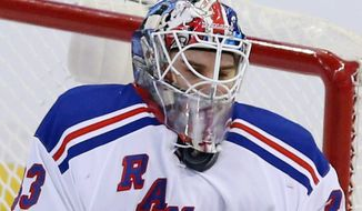 New York Rangers goaltender Cam Talbot (33) stops the puck under his facemask during the second period of an NHL hockey game against the Ottawa Senators in Ottawa, Saturday, Jan. 18, 2014. (AP Photo/The Canadian Press, Fred Chartrand)