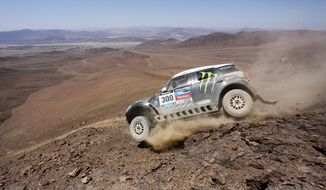 Mini driver Stephane Peterhansel and co-pilot Jean Paul Cottret, both of France, drive down a mountain during the eleventh stage of the Dakar Rally between the cities of Antofagasta and El Salvador, Chile, Thursday, Jan. 16, 2014. (AP Photo/Victor R. Caivano)