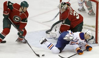 Minnesota Wild defenseman Clayton Stoner, left, clears a rebound as Wild goalie Darcy Kuemper (35) covers the net and Edmonton Oilers right wing Jordan Eberle (14) falls during the first period of an NHL hockey game in St. Paul, Minn., Thursday, Jan. 16, 2014. (AP Photo/Ann Heisenfelt)