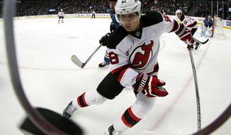 New Jersey Devils right wing Dainius Zubrus, of Lithuania, pursues a puck against the Colorado Avalanche in the first period of an NHL hockey game in Denver, Thursday, Jan. 16, 2014. (AP Photo/David Zalubowski)