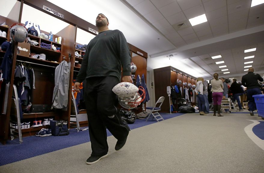 New England Patriots rookie free-agent, defensive tackle Joe Vellano,  walks past quarterback Tom Brady's locker carrying an autographed team ball and a helmet at the NFL football team's facility in Foxborough, Mass., Monday, Jan. 20, 2014. The Patriots lost to the Denver Broncos in the AFC Championship game Sunday in Denver ending their season. (AP Photo/Stephan Savoia)