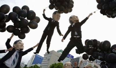 Members of international relief group Oxfam, dressed as G-8 leaders, hold balloons representing the amount of carbon the countries emit per capita, near the summit in Japan on Tuesday. (Associated Press)