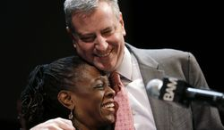 """New York City Mayor Bill de Blasio hugs his wife Chirlane McCray at a tribute to Martin Luther King, Jr. in the Brooklyn borough of New York, Monday, Jan. 20, 2014. De Blasio told a packed audience Monday at the Brooklyn Academy of Music that the """"price of inequality has deepened."""" The mayor says economic inequality is closing doors for hard-working people in the city and around the country. (AP Photo/Seth Wenig)"""