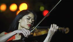 FIL:E - This is a Monday, Oct. 18, 2010 file photo of Internationally renown  violinist Vanessa Mae as she performs during her concert in Prague, Czech Republic. The manager of musician Vanessa Mae says the musician will be swapping her violin for skis to compete at the Winter Olympics. Giles Howard says the classical-pop violinist has qualified for the Thai team at the Sochi games. The International Ski Federation published rankings on Monday Jan. 20, 2014 confirming Mae has met the qualifying criteria to compete at Sochi. (AP Photo/CTK, Rene Volfik) ** SLOVAKIA OUT **