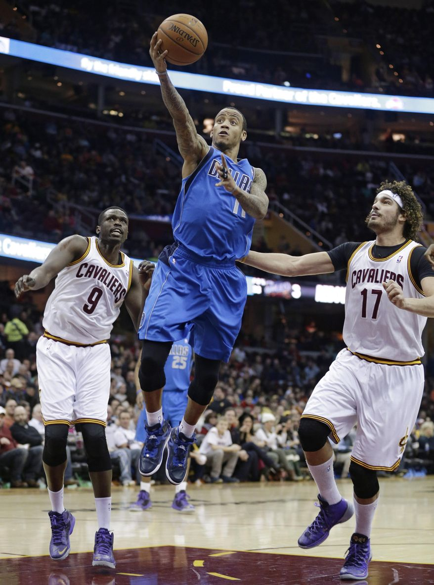Dallas Mavericks' Monta Ellis (11) shoots between Cleveland Cavaliers' Loul Deng, (9) from Sudan, and Cleveland Cavaliers' Anderson Varejao (17), from Brazil, during the first quarter of an NBA basketball game Monday, Jan. 20, 2014, in Cleveland. (AP Photo/Tony Dejak)