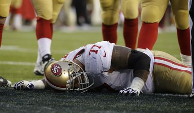 San Francisco 49ers' Mike Iupati lays on the field after being hurt during the first half of the NFL football NFC Championship game against the Seattle Seahawks, Sunday, Jan. 19, 2014, in Seattle. (AP Photo/Ted S. Warren)