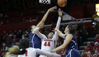 Rutgers forward Betnijah Laney (44) takes a shot as she splits Connecticut defenders Kiah Stokes and Stefanie Dolson, right, during the first half of an NCAA college basketball game Sunday, Jan. 19, 2014, in Piscataway, N.J. (AP Photo/Mel Evans)