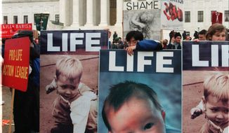 """Joe Park, center, of Chicago, Ill., leans on a anti-abortion sign in front of the Supreme Court Friday, Jan. 22, 1999, during the annual, """"March for Life""""  rally in Washington. A large crowd of abortion foes are taking part in the rally. (AP Photo/Joel Rennich)"""