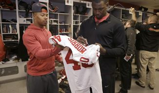 San Francisco 49ers linebacker Aldon Smith, right, signs a jersey for defensive back Darryl Morris in the locker room at an NFL training facility in Santa Clara, Calif., Monday, Jan. 20, 2014. The 49ers lost to the Seattle Seahawks in the NFC Championship Game. (AP Photo/Jeff Chiu)