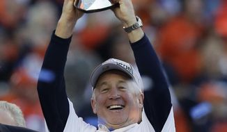 Denver Broncos head coach John Fox celebrates with the trophy after the AFC Championship NFL playoff football game against the New England Patriots in Denver, Sunday, Jan. 19, 2014. The Broncos defeated the Patriots 26-16 to advance to the Super Bowl. (AP Photo/Julie Jacobson)