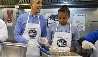 President Barack Obama and his daughter Sasha, right, make burritos at DC Central Kitchen as part of a service project in honor of Martin Luther King, Jr. Day,  Monday, Jan. 20, 2014, in Washington. Also helping were first lady Michelle Obama and daughter Malia Obama. (AP Photo/Jacquelyn Martin)