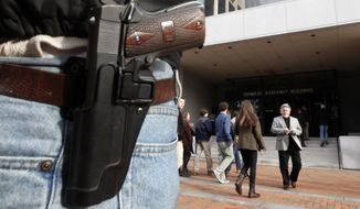 A Springfield model 1911 .45acp pistol, foreground, is worn by gun-rights advocate John Savarese, from Chesterfield County, Va., as he stands outside the General Assembly Building in Richmond, Va., Monday, Jan. 20, 2014. This is the day that   gun rights groups  and gun control groups will lobby members of the Virginia General Assembly at Capitol Square, where open carry of firearms is approved. (AP Photo/Richmond Times-Dispatch, Bob Brown)