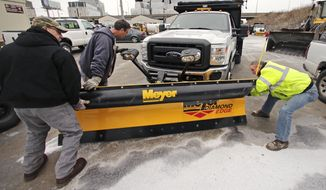 Workers from the Mass. Dept. of Conservation and Recreation put a plow on a truck in advance of an expected winter snow storm Tuesday, Jan. 21, 2014, in Cambridge, Mass.  The Boston area is expected to get about a foot of snow by Wednesday evening. (AP Photo/Charles Krupa)