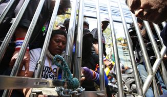 Thai anti-government protesters use chain to lock up the gate at the fishery department as they close down the office Tuesday, Jan. 21, 2014 in Bangkok, Thailand. Twin explosions shook an anti-government demonstration site in Thailand's capital, wounding more than dozens of people in the latest violence to hit Bangkok as the nation's increasingly bloody political crisis drags on. (AP Photo/Wason Wanichakorn)