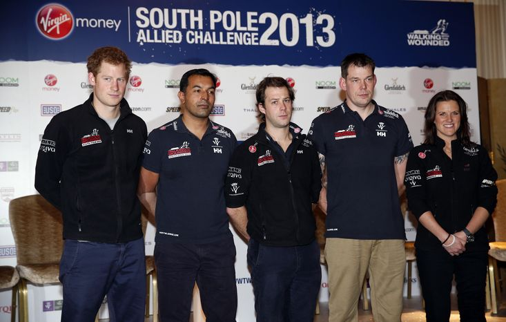 Britain's Prince Harry, left, the Expedition Patron, poses with from left, Ibrar Ali, Guy Disney and Kate Philp,  members of the Walking With The Wounded South Pole Allied Challenge 2013 team following a welcome home news conference, in central  London, Tuesday, Jan. 21, 2014. The Walking With The Wounded Virgin Money South Pole Allied Challenge 2013 concluded on Friday 13 December, when three teams of wounded servicemen and women successfully reached the South Pole after crossing 200km of Antarctic plateau. (AP Photo/Lefteris Pitarakis, Pool)