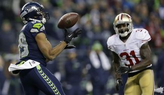 Seattle Seahawks' Doug Baldwin catches a pass in front of San Francisco 49ers' Donte Whitner (31) during the first half of the NFL football NFC Championship game, Sunday, Jan. 19, 2014, in Seattle. (AP Photo/Marcio Jose Sanchez)