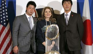 U.S. Ambassador to Japan Caroline Kennedy, center, Boston Red Sox pitchers Junichi Tazawa, left, and Koji Uehara pose for photos with the World Series trophy at the U.S. embassy in Tokyo, Tuesday, Jan. 21, 2014.  (AP Photo/Toru Hanai, Pool)