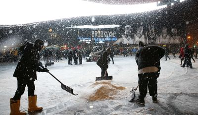 Workers shovel snow in front of Brooklyn's Barclay's Center before an NBA basketball game between the Orlando Magic and the Brooklyn Nets at the Barclays Center, Tuesday, Jan. 21, 2014 in New York. (AP Photo/Kathy Willens)