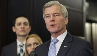 Former Virginia Gov. Bob McDonnell makes a statement as his daughter, Cailin and her husband, Chris Young, listen during a news conference in Richmond, Va., Tuesday, Jan. 21, 2014.  McDonnell and his wife were indicted Tuesday on corruption charges after a monthslong federal investigation into gifts the Republican received from a political donor.  (AP Photo/Steve Helber)