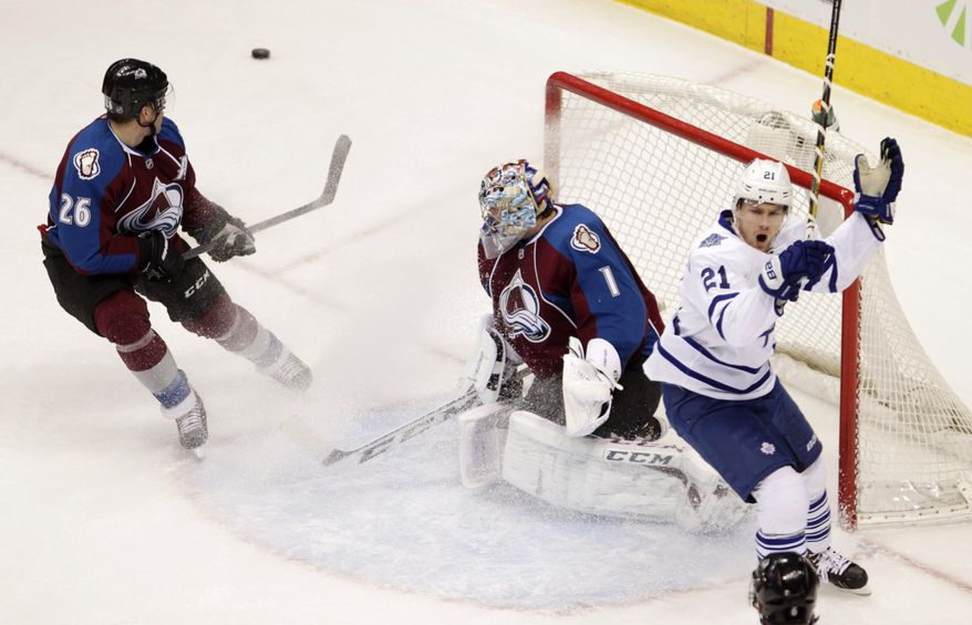 Toronto Maple Leafs left wing James van Riemsdyk (21) looks to the referee as Colorado Avalanche center Paul Stastny (26) defends the crease and Avalanche goalie Semyon Varlamov (1) deflects the puck during the second period of an NHL game in Denver on Tuesday, Jan. 21, 2014. Stasny was called for a hooking penalty on the play. (AP Photo/Joe Mahoney)