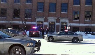 Police investigate reports of a shooting at Purdue University in West Lafayette, Ind., on Tuesday, Jan. 21, 2014. Police say they have a person in custody and the university says it told people to take shelter and have cleared the building as the area is searched. (AP Photo/The Journal & Courier, John Terhune)