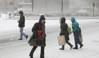 Pedestrians make their way through the snow in the Manhattan borough of New York, Tuesday, Jan. 21, 2014.  The National Weather Service said the storm could bring 10 to 14 inches of snow to Philadelphia and southern New England and up to a foot in New York City, to be followed by bitter cold. An arctic air mass will plunge the eastern half of the United States into a deep freeze, with wind chills as low as 40 degrees below zero, the weather service said.  (AP Photo/Seth Wenig)